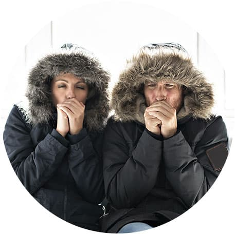 a couple in winter coats blowing in their hands